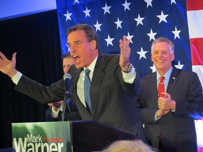 U.S. Sen. Mark Warner, with Don Beyer and Gov. Terry McAuliffe behind him, addresses the crowd on election night.