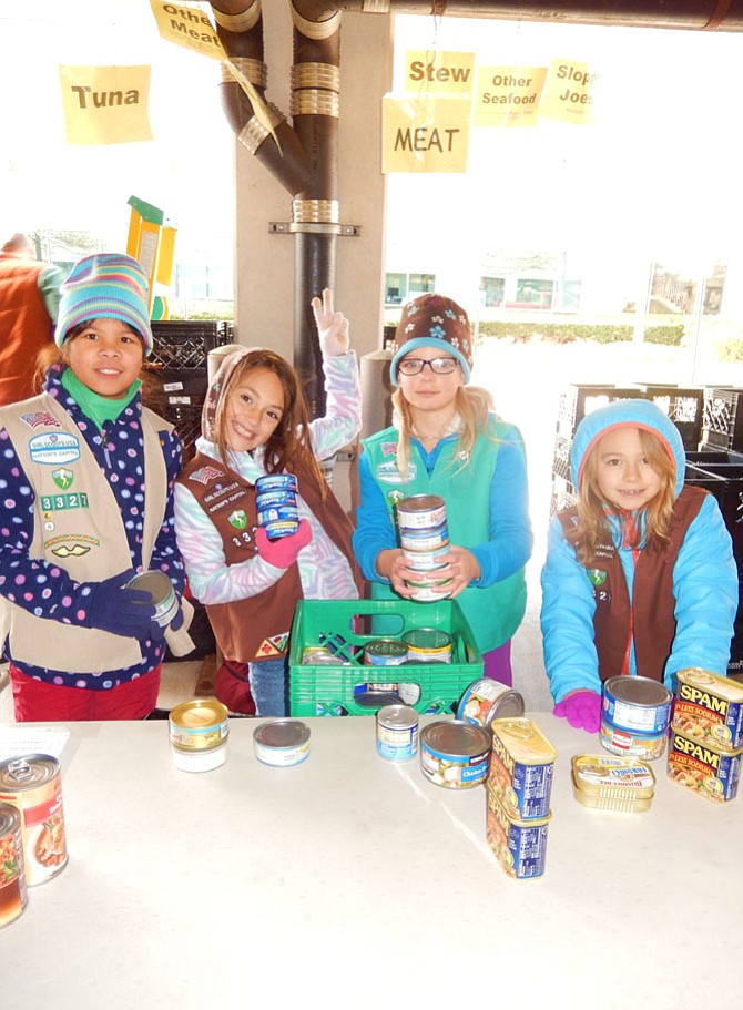 Helping are Centreville homeschool Scout Troop 3327 members (from left) Elisabeth Keeley, 11; Stella Pettit, 9; Juliet DeLap, 9 and Ruth Moran, 8.