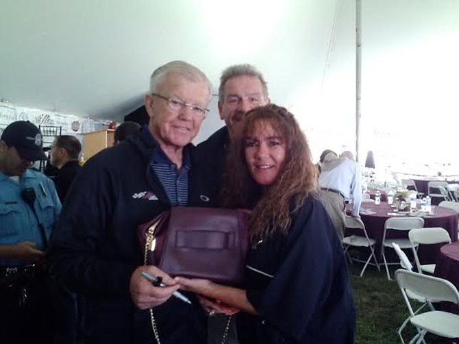 (From left) Former Redskins head coach Joe Gibbs, Redskin Ron Saul and Saul's wife Robin Robison raise awareness for domestic violence with the Kerry Washington-designed purple purse.