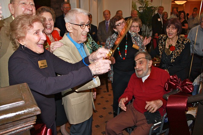 Residents Betty Ogg, Tom Rainey and Marc Nevenstone cheer after cutting the ribbon during Brightview Senior Living's grand opening.