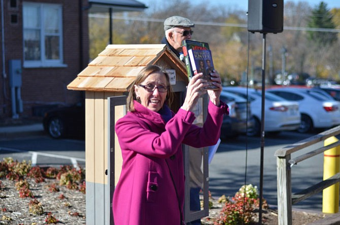 Herndon resident Mercia Hobson, a member of the Herndon Rotary Club, displays some books available at Herndon's first Little Free Library on Saturday, Nov. 15. There are three shelves for donated books in the weatherproof box for books.