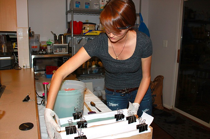 Brooke Goad smooths the soap into the mold after making a batch. Brooke is a co-owner of The Soap Engineers.