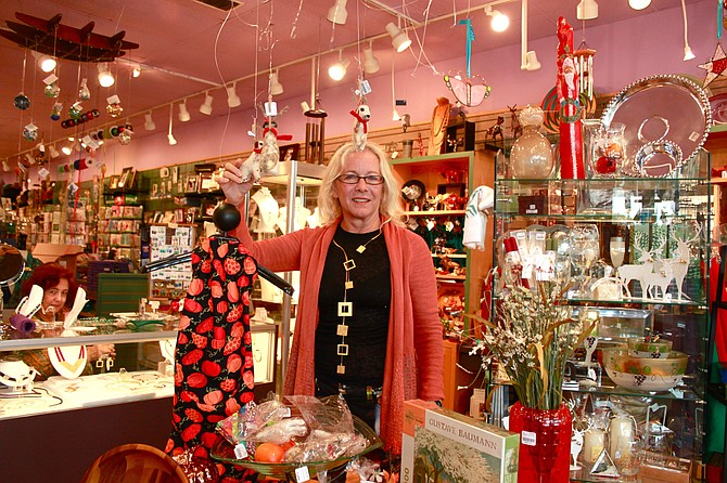 The Artisans co-owner, Shannon Denny Price, hangs up some of the new felt ornaments in the shop.