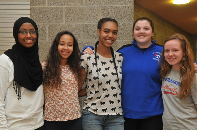 T.C. Williams varsity softball players Amal Bouh, Calla Zane, Shayla Brown, Amanda Dorris and Kayla Schelley greet shoppers and offer raffle tickets for sale at the annual holiday craft fair last Saturday.
