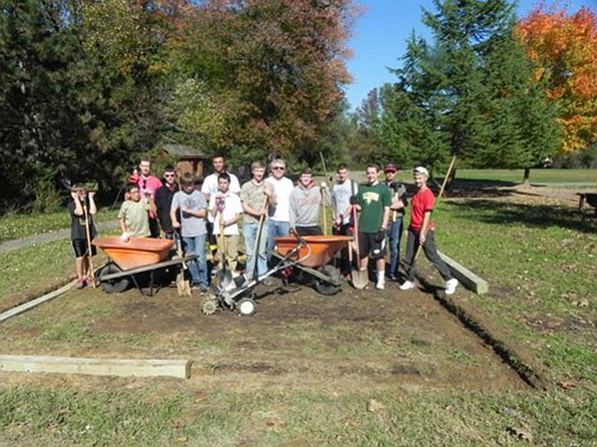 Troop 128 members and family members who created a gravel bed for Churchill Road's composters are (from left to right): Luke Carlisle, Waleed Khartami, George Carter, Reilly Jeddy,  Walker Haynes, Simon Suttcliffe, Connor Yuzon, Jake Holzapfel, Jed Holzapfel, Garrison Edwards, Christian Markwart, Will Arrison, Luther Markwart and Betsy Stone.