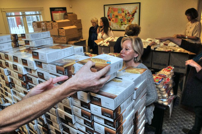 The Keller Williams Realty team and volunteers numbering over 75 spent Tuesday, Nov. 26, sorting and repacking the fixings for 435 Thanksgiving meals at the Keller Williams offices on S. Washington Street.