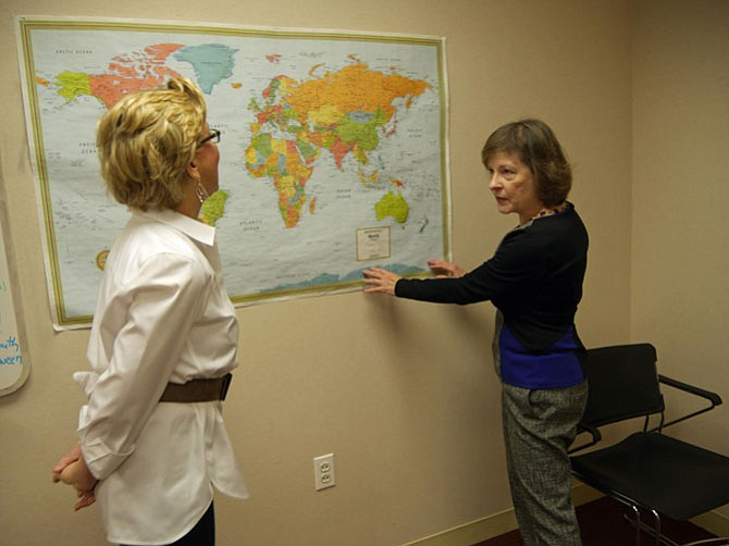 Patricia DePuy and Marcia D'Arcangelo pinpoint new countries, previously unheard of, where immigrants have come from to join the New Neighbors ELL program held in donated space at the Christ Church's Fowler Center.