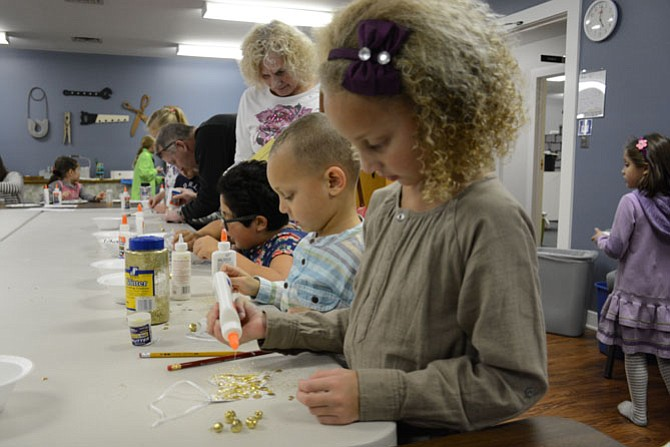 Chase Olaf Watkins (center, TOT pre-school at Sydenstricker United Methodist Church) and Ada Mae Watkins (right, first grade at Orange Hunt Elementary School) of Springfield decorate Chrismon symbol ornaments at Burke United Methodist Church.