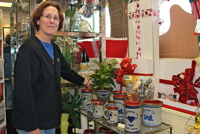 Herndon Florist sales associate Bobbe Duquette showcases the Herndon pottery featured in the shop, ready to buy or to be filled with flowers.