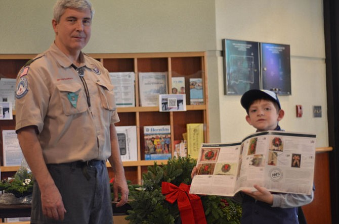 Cub Scout Pack 157 leader Barry Dresdner with Cub Scout Michael Fullerton helped sell wreaths at the Herndon Annual Arts and Crafts Show on Sunday, Dec. 7.