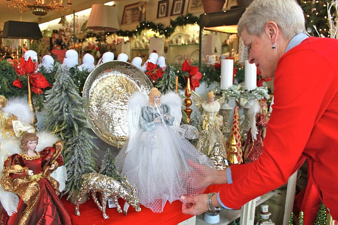Nora Arquin, Mesmeralda's Gifts part-time manager, fixes the placement of a tree topper in the store.
