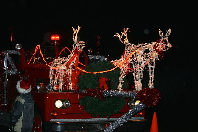 Rudolph led the arrival of Santa's sleigh aboard an antique fire truck.