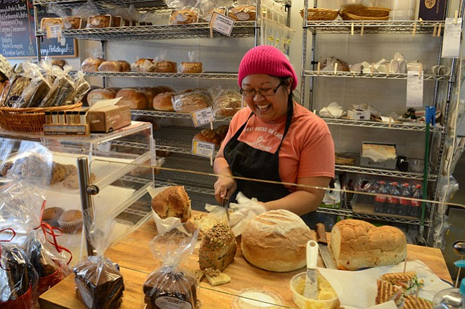 Mali Soderborg of Fairfax cuts a free sample slice of Extreme Cinnamon bread for a customer at Great Harvest Bread Company in Burke.