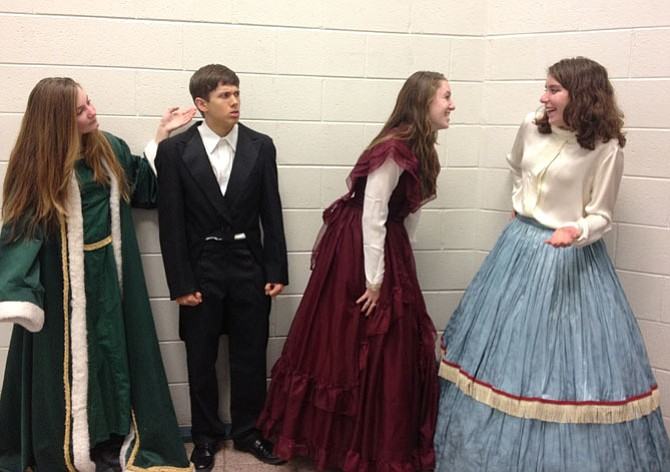 As the Ghost of Christmas Present, Hannah Grudi shows Scrooge (Ryan Rickard) two women (Maddy Farmer and Kate Meyer) being happy.