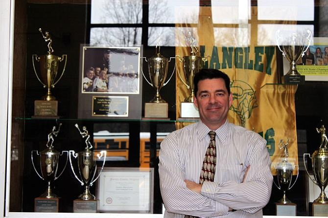 Langley High School Principal Matt Ragone in front of the school trophy case.
