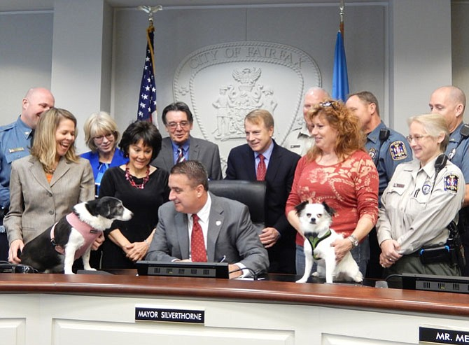 What do you think about that? Both dogs and animal advocates watch Mayor Scott Silverthorne sign the tethering ordinance into law, Monday, Dec. 15.