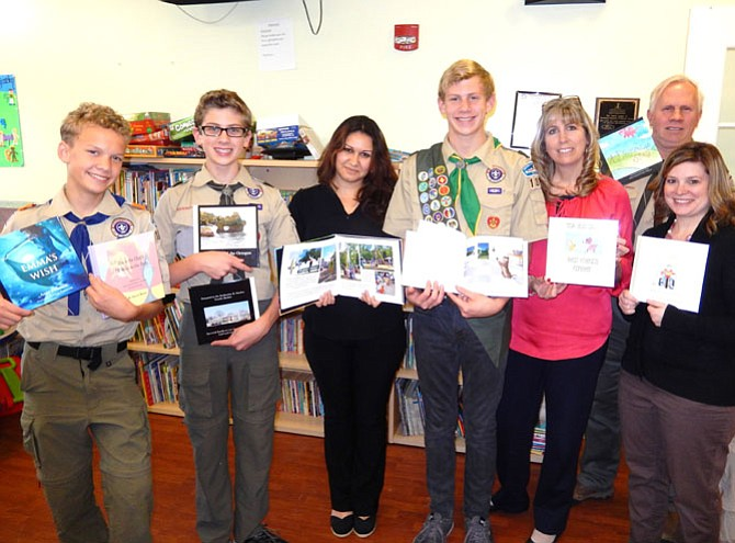 Showing the covers and some of the inside pages of the books are (from left) Boy Scout Drake Wilkinson, Braeden Anderson (Garrett's brother), Nurjan Ahmedova, Garrett Anderson, Becky and Brent Anderson (his parents), and Amy Baldwin (his cousin).