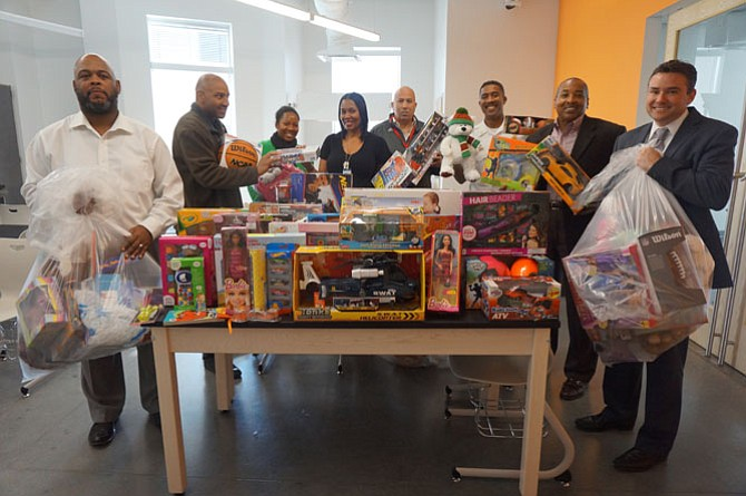 Jefferson-Houston Elementary School principal Chris Phillips, right, accepts toys donated to his students by members of the Departmental Progressive Club on Dec. 15. Pictured with him are Sherman Deck, Norman Reynolds, school social workers Karima Wade and Arnecia Moody, Willie Bailey and Merrick Malone.