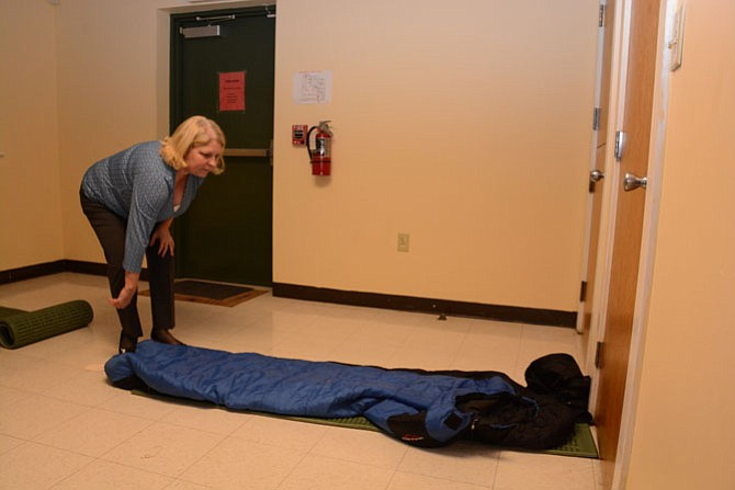 Sherry Edelkamp of Alexandria rolls out sleeping bags at Rising Hope Mission Church, a shelter site for New Hope Housing.