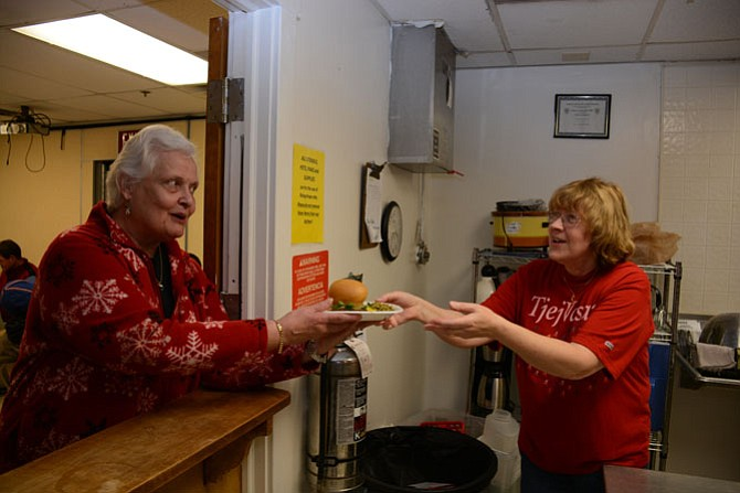 Mount Vernon residents and members of Aldersgate United Methodist Church Karen Latta (left) and Gunnel Hamilton (right) pass plates of food to be served to overnight guests of Rising Hope Mission Church.