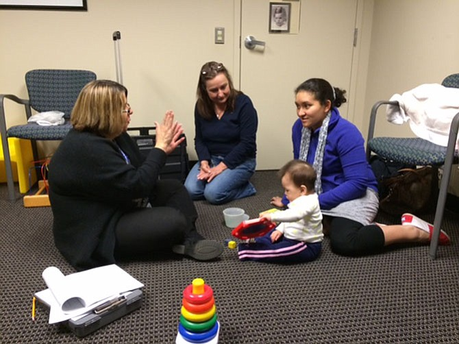 CSB's Infant and Toddler Connection interventionists Olga Jiminez and Belkis Negron explain development to mother Cecie and daughter Allison.