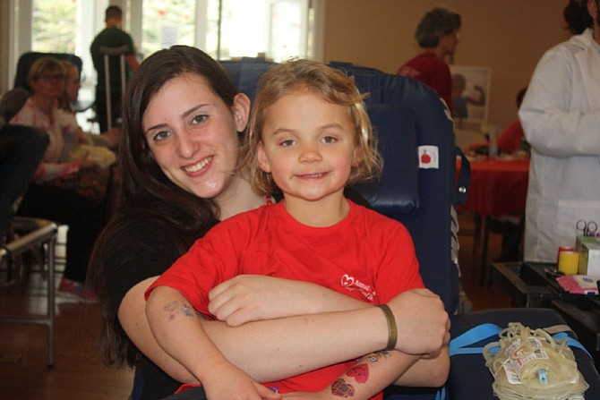 Robinson sophomore Madeline Dozier waits to donate blood for the first time, with the drive's namesake Sadie Lauer.