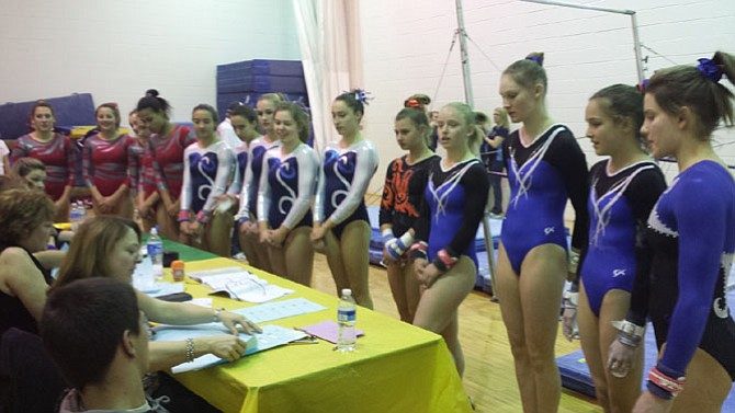 Conference 6 gymnasts check in before their bar routines during the 6A North region championship meet on Feb. 11 at Lake Braddock Secondary School.