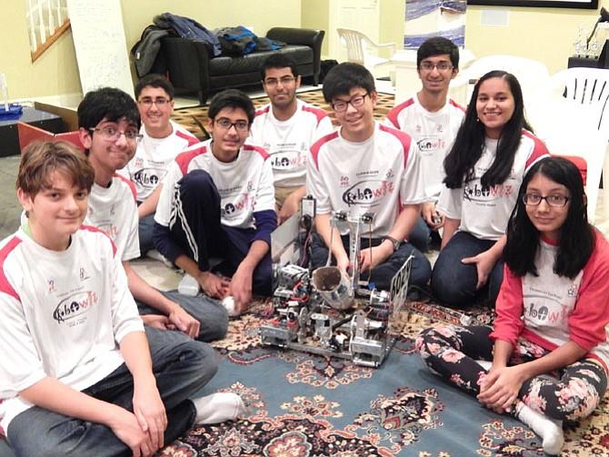 Surrounding their robot are (from left) Cedric Bernard, Shomik Ghose, Saarthak Sethi, Josal Patel, Abhishek Mishra, Jami Park, Adarsh Kulkarni, Radhika Agrawal and Anushka Jain.