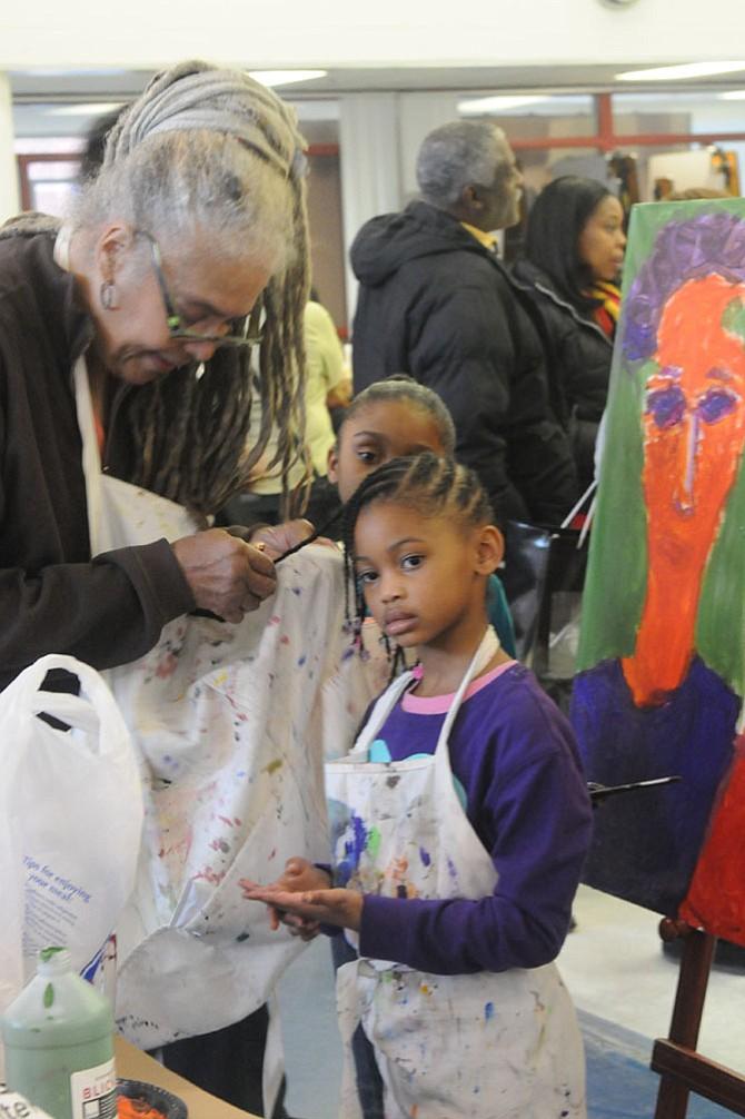 Artist Eleanor Johnson helps unpaint Jasmine Terry's hair after Jasmine finished painting.