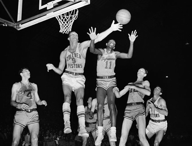 Playing for the Syracuse Nationals, Earl Lloyd (11), battles Fort Wayne's Mel Hutchins (9) for a rebound during an NBA championship game on April 5, 1955. With the series victory, Lloyd and teammate Jim Tucker became the first African Americans to become NBA champions.