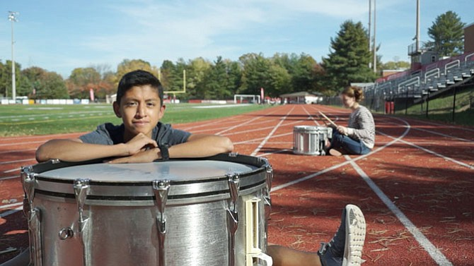 Conor Zeya with his drum named Evan, and Jade Deatherage in the background.