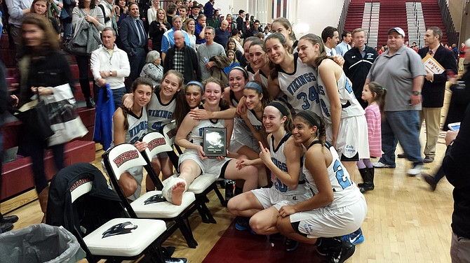Members of the Whitman girls' basketball team celebrate winning the 4A West region championship with injured teammate Marie Hatch on Monday night at Paint Branch High School.