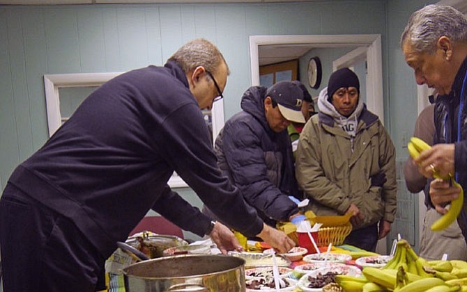 The Rev. Mark Suriano, associate minister at Rock Spring UCC, dishes out black beans and rice on Feb. 10 to about 40 day laborers in the Shirlington Employment and Education Center (SEEC).