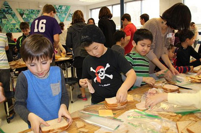 Churchill Road first graders Ellis Farah, Bowen Han and Carlos Janada form an assembly line to make sandwiches for Martha's Table.