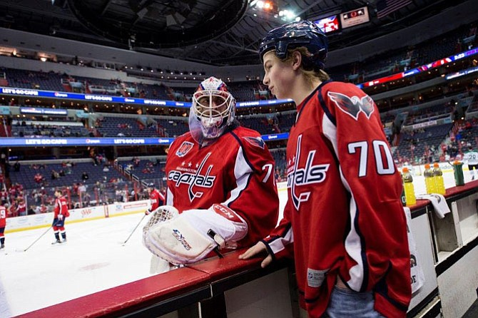 Washington Capitals goaltender Braden Holtby greets 13-year-old Healy, Alaska, native Caleb Graham as Graham watches warmups from the Capitals' bench prior to the team's March 13 game against the Dallas Stars at Verizon Center in Washington, D.C. Graham suffers from a life-threatening heart condition and had his wish to meet Holtby granted by Make-A-Wish.