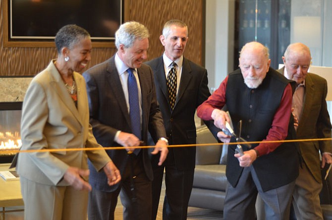 "Reston founder Bob Simon holding the scissors for the Saturday, March 14 ribbon cutting for the Harrison Apartments by Reston Parkway in Reston. Also in the picture are Supervisor Catherine M. Hudgins (D-Hunter Mill), Renaissance Centro managing members Albert H. ""Sonny"" Small and Douglas Erdman, and Albert H. Small."