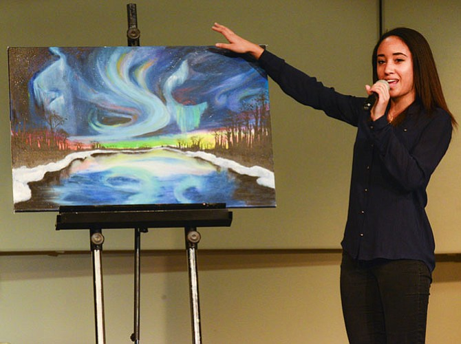 "Kiana Cauley of Arlington, explaining her original artwork done in tempura and oil titled ""Northern Lights."""