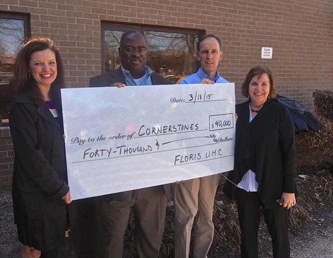From left -- Cornerstones Chairman of the Board Jill Norcross, COO Greg White, Floris UMC Lead Pastor, Rev. Tom Berlin, and Cornerstones CEO Kerrie Wilson pose with the mock up check representing the $40,000 donation made to Cornerstones by the members of Floris United Methodist Church in Herndon. Each year, Floris donates its Christmas Eve offerings to a nonprofit partner or to a special need or cause in the community or around the globe. The Floris members have been making this donation for more than 10 years.