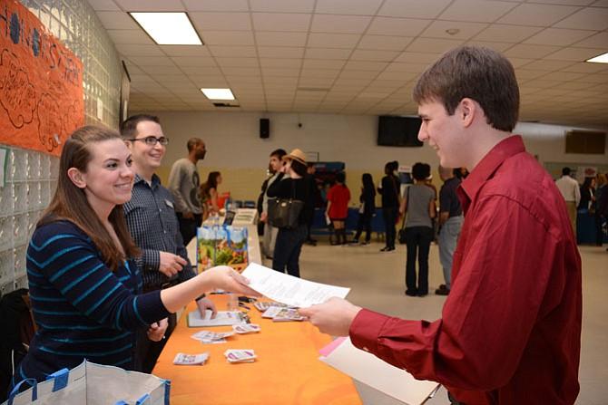 Wegmans recruiter Janet Walker (left) receives a resume from hopeful applicant Jackson Muse of Fairfax (right).