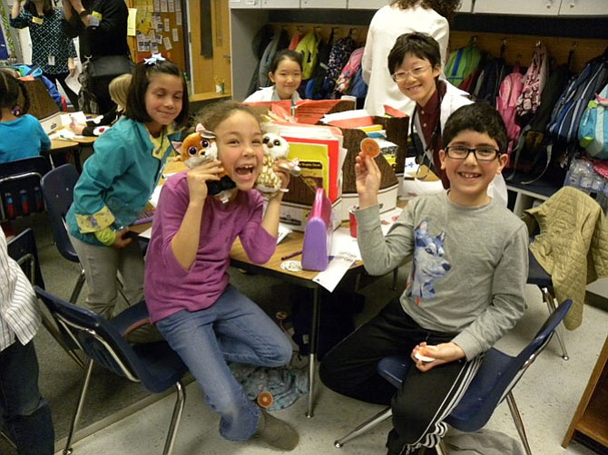"Alexandra Lujan's second grade class at Westbriar Elementary School in Vienna learn about the businesses in the community during Junior Achievement of Greater Washington's ""JA in a Day"" program. From left, Ariana, Sophia, Abdullah and Jay create a new doughnut flavor to attract customers to their shop."