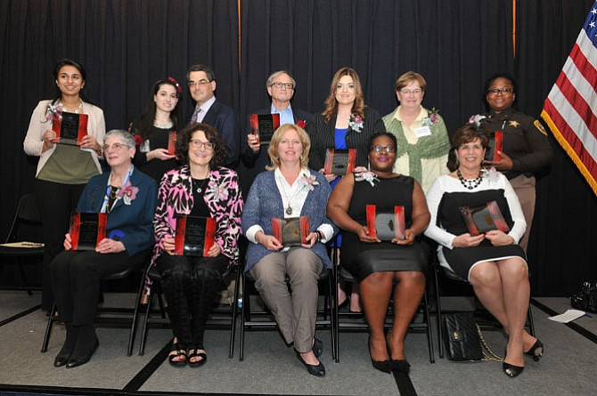 The 2015 Salute to Women Awards honorees include (back row from left): Zauhirah Tipu, Rebecca Nash (daughter of Laurie Meyer), Robert Nash (husband of Laurie Meyer), Ed Singer (husband of Joan Singer), Ashley McNeff Behrens, Ginny Hill-Obranovich and Valarie Wright. Front row from left: Brooksie Koopman, Lorraine Friedman, Cynthia Anderson, LaDonna Sanders and Suzanne Maxey.