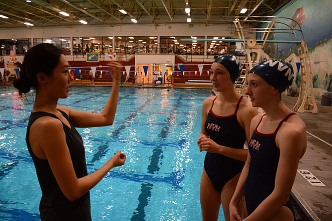 Coach Hayan Kim (left), of Fairfax, gives Robinson junior Jackie Hafner (center) and Woodson junior Margot Baden (right) technique advice for their duet routine.