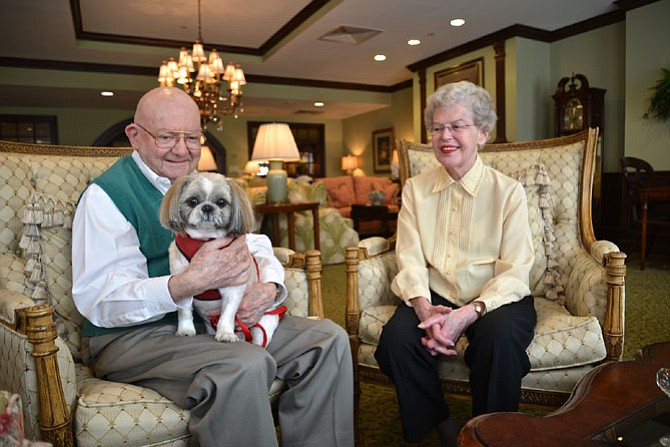 In the lounge at The Woodlands Retirement Community in Fairfax, Col. James McAllan (US Army-Ret) with Riley on his lap and Linda McAllan offered up some thoughts on their senior community living experience. The McAllans were celebrating their Woodlands one-year anniversary that day.