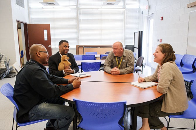 Alexandria Deputy Director of Administration Alfred Coleman holds a puppy as he talks with city team members Pelham Park (left) and Kevin Jones and AWLA Director of Animal Care Abbie Hubbard.