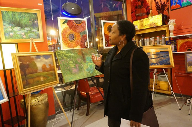 Anita McFadden of Fairfax browses the artwork during the Breath of Spring reception March 19 at Artfully Chocolate.