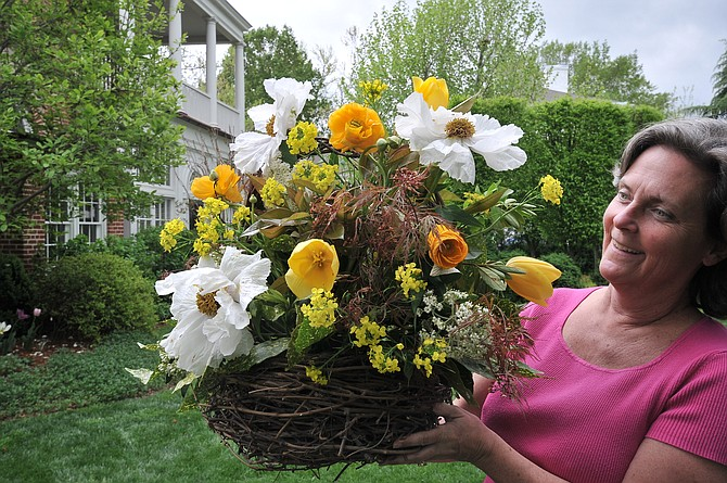 Lucy Goddin displays a finished arrangement to be displayed in a garden.