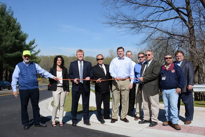 From left, Lee Schmidt, Burke Ponds trustee; Renée Mumford, Burke Landings trustee; Supervisor John Cook (R-Braddock); Paul Viano, Burke Centre Station community manager; Patrick Gloyd, Burke Centre executive director; Tim Conley, Fairfax County Department of Transportation; Chris Wells, Fairfax County Department of Transportation; James Horstman, Fairfax County Utilities Design & Construction; Ken Atkins, Fairfax County Utilities Design & Construction and John Honnick, Fairfax County Land Acquisition, cut the ribbon officially opening a new stretch of sidewalk along Burke Commons Road.