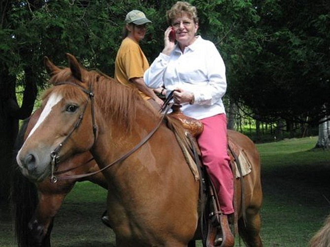 Karen Brown multitasks riding a horse and talking on a Blackberry.