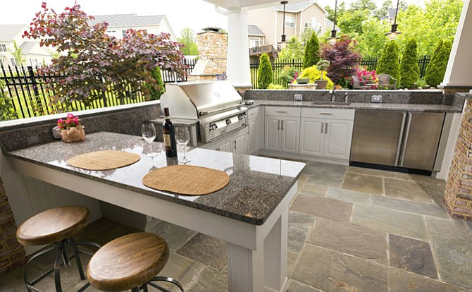 The outdoor kitchen to this poolside solution is equipped with both a traditional grill and a power burner. There's also dining for two; a refrigerator and many amenities.