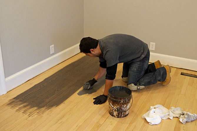 Roberto Melgar from M&M Floors puts test stains on the hardwood floors to match the walls.